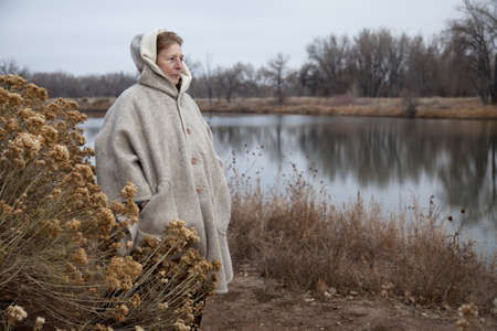 senior woman in her eighties enjoys a walk and watching wildlife  on a lake shore, nostalgic late fall scenery in Fort Collins, Colorado Stock Photo - 8265005