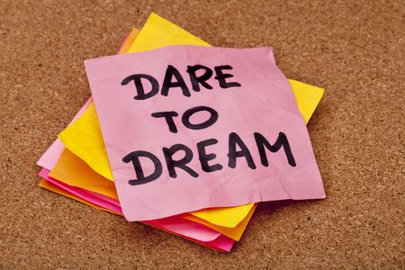 dare to dream, motivational slogan, colorful sticky notes on cork bulletin board
