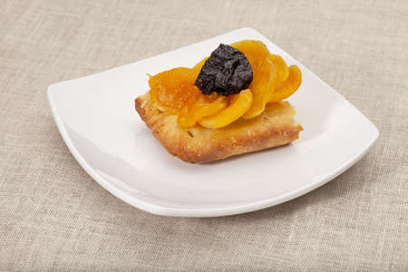 a portion of homemade fruit tart with apricot and prune on a square white plate against tablecloth