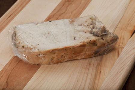 een portie gesteunde kalkoenfilet verpakt in plastic folie voor opslag in een koelkast of vriezer, snijplankachtergrond