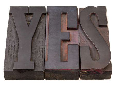 yes - word in antique wooden letterpress printing blocks, stained by dark color inks, isolated on white