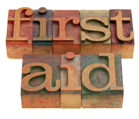 first aid - words in vintage wooden letterpress printing blocks, stained by color inks, isolated on white
