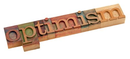 optimism word in vintage wooden letterpress printing blocks, stained by color inks, isolated on white Stock Photo - 8378957