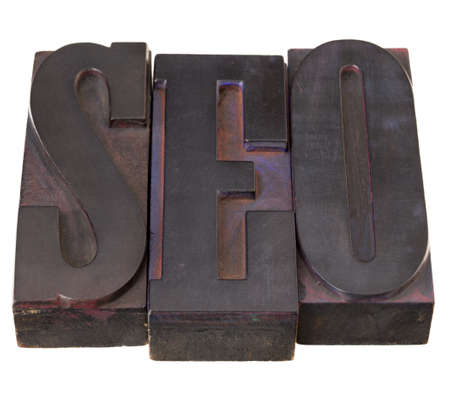 SEO (search engine optimization ) acronym - word in antique letterpress printing blocks, stained by color inks, isolated on white Stock Photo - 8414191