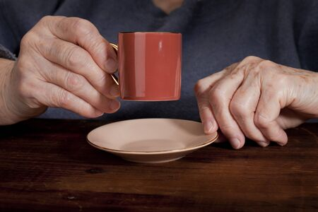 senior woman hands with espresso coffee cup against old grunge wooden table Stock Photo - 8414195