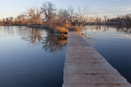 boardwalk trail: nature trail - boardwalk pathway over lake in old gravel quarry converted into park (Riverbend Ponds in Fort Collins, Colorado), late fall or early winter scenery with some snow and ice