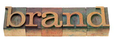 白で隔離され、ヴィンテージの木製活版印刷ブロックには、カラー インクで染色ブランド単語 写真素材