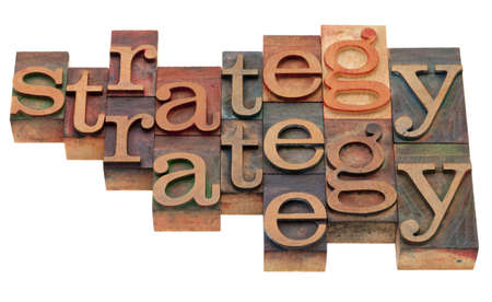 strategy word abstract in vintage wooden letterpress printing blocks, stained by color inks, isolated on white Stock Photo - 8471652