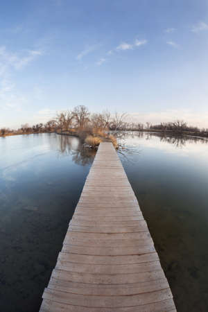 pathway, journey or goal concept - boardwalk and trail across lake and swamp, wide angle fisheye lens perspective, late fall scenery with ice cover Stock Photo - 8499210