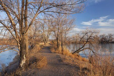 pathway on a narrow dike between lakes, late fall or winter scenery with ice cover, Riverbend Ponds Nature Area, Fort Collins, Colorado Stock Photo - 8499211