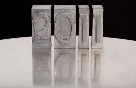 New Year concept - 2011 word in vintage metal lettepress printing blcoks with reflection in grunge silver surface Stock Photo - 8533209
