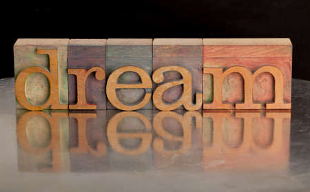 dream word abstract in vintage wood letterpress printing blocks with reflection in grunge silver surface
