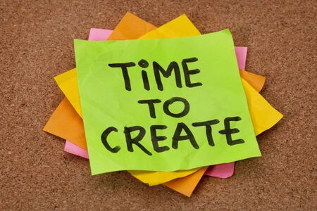 creativity concept - time to create reminder on a stack of sticky notes against cork bulletin board