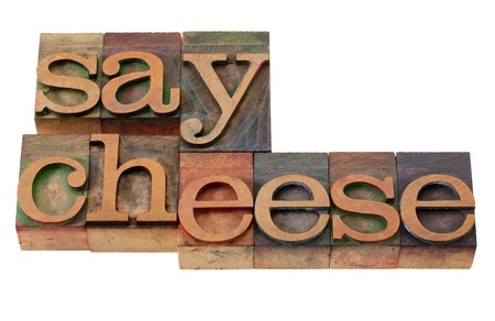 say cheese phrase in vintage wooden letterpress printing blocks, stained by color inks, isolated on white