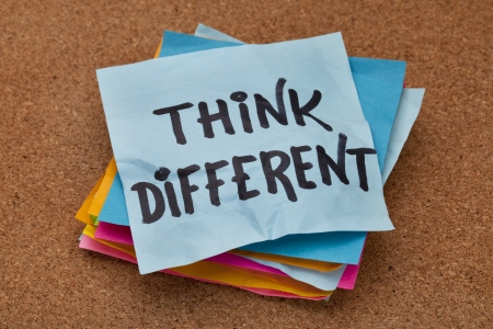 motivational: think different concept - motivational phrase on a stack of sticky notes against cork bulletin board