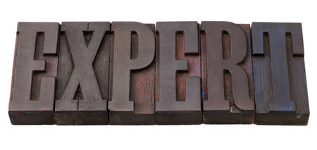 expert word in antique wooden letterpress printing blocks, stained by color inks, isolated on white