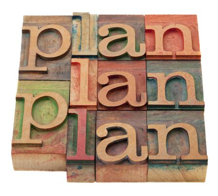 plan word abstract in vintage wooden letterpress printing blocks, stained by color inks, isolated on white photo