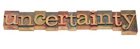 hesitancy: uncertainty word in vintage wooden letterpress printing blocks, stained by color inks, isolated on white