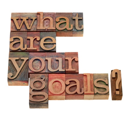 letterpress words: what are your goals question in vintage wooden letterpress printing blocks, stained by color inks, isolated on white Stock Photo