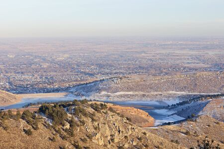 typical hazy winter afternoon over Fort Collins, Colorado with frozen Horsetooth Reservoir, some snow, clear sky, but with a brown layer of dust and aerosols in the air Stock Photo - 8612731
