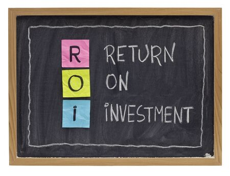 ROI - return on investment acronym explained with color sticky notes and white chalk handwriting on blackboard Banco de Imagens