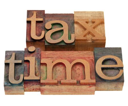 tax time words in vintage wooden letterpress printing blocks, stained by color inks, isolated on white Imagens