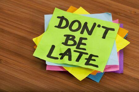 llegar tarde: no ser final recordatorio - bloque de notas rápidas de color sobre fondo de madera (bambú) Foto de archivo