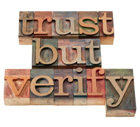 phrase: trust but verify  quote from  Ronald Reagan concerning relations with Soviet Union - vintage wooden letterpress printing blocks, stained by color inks, isolated on white Stock Photo