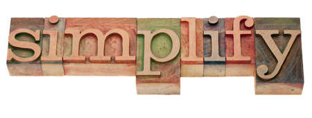 simplify- word in vintage wooden letterpress printing blocks, stained by color inks, isolated on white Stock Photo - 8801395