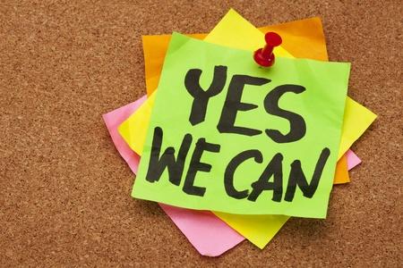 optimismo: s� podemos - lema motivacional en una pila de notas adhesivas, publicado en el tabl�n de corcho Foto de archivo