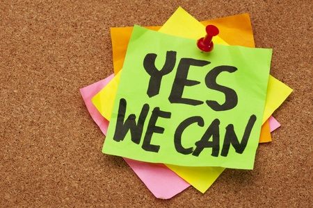 otimismo: yes we can - motivational slogan on a stack of sticky notes posted on cork bulletin board Banco de Imagens
