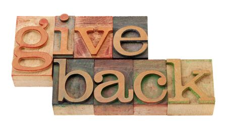 give back - words in vintage wooden letterpress printing blocks, stained by color inks, isolated on white Foto de archivo