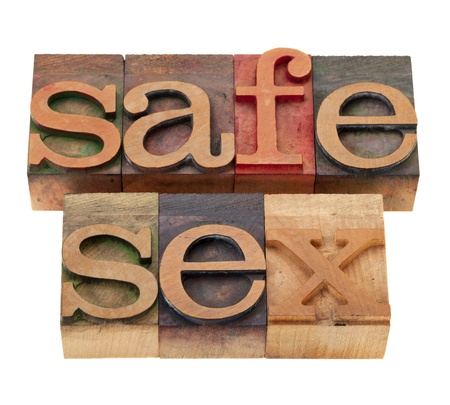 safe sex slogan in vintage wooden letterpress printing blocks, stained by color inks, isolated on white