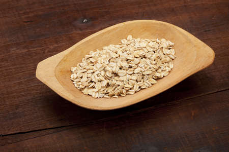rolled oats on a rustic wooden bowl against old and cracked table Stock Photo - 8908178