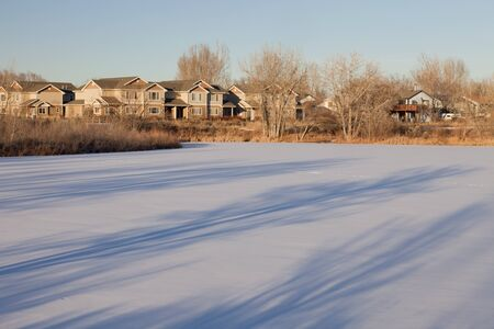 housing development and lake natural area in Fort Collins, Colorado, afternoon winter scenery with long tree shadows Stock Photo - 8908210