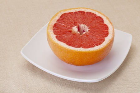 half of red grapefruit on white square bowl against tablecloth Stock Photo - 8908218