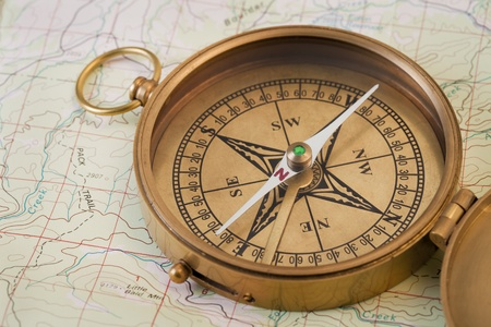 magnetic north: vintage pocket brass compass opened over topographical map