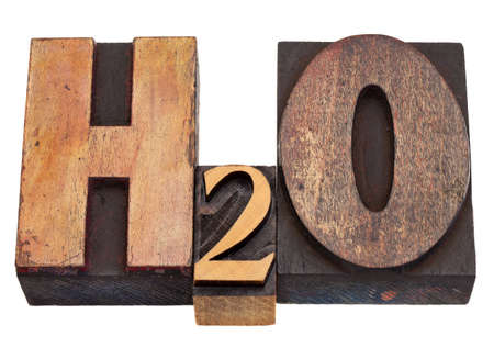 water stained: H2O - water chemical symbol in vintage wood letterpress printing blocks, stained by color inks, isolated on white Stock Photo