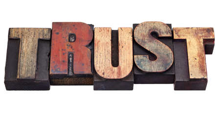 trust: trust word in vintage grunge wooden letterpress printing blocks, isolated on white