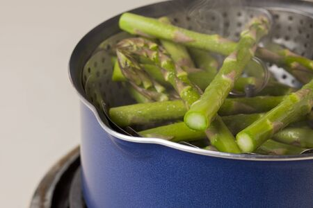 steaming green asparagus in a steamer basket inside blue pot photo
