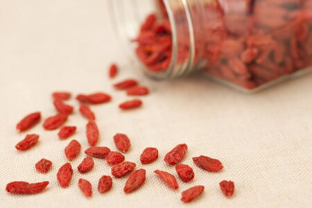 berry: dried Tibetan goji berries (wolfberries) spilling from a glass jar, shallow depth of field