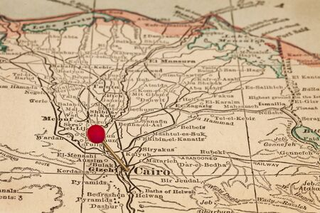 map pin: Cairo, Egypt and delta of Nile River, on vintage 1920s map with a red pushpin, selective focus