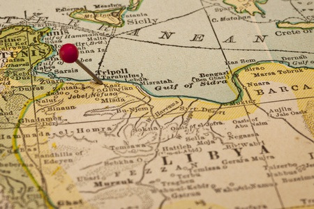 red pushpin: Libya and Tripoli on vintage 1920s map with a red pushpin, selective focus  Stock Photo