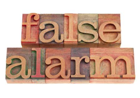 false alarm words in vintage wood letterpress printing blocks, isolated on white Stock Photo - 9063432