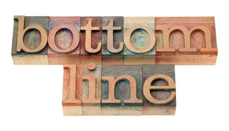 net profit or loss concept - bottom line words in vintage wooden letterpress printing blocks, stained by color inks, isolated on white Banco de Imagens