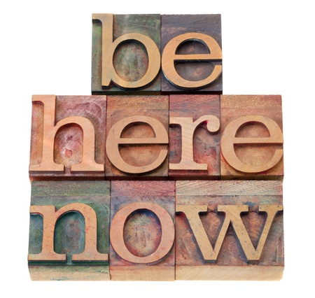 letterpress type: be here now - motivational reminder - words  in vintage wood letterpress printing blocks, isolated on white