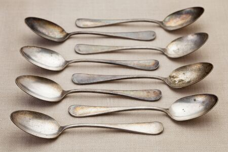 patina: old grunge silver spoons with scratches and patina on tablecloth, shallow depth of field Stock Photo