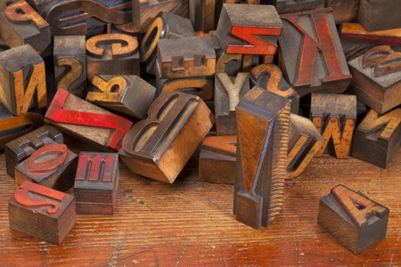 exclamation point: a variety of vintage wooden letterpress printing blocks, stained by color inks,  placed randomly on an old wood surface, focus on exclamation point Stock Photo