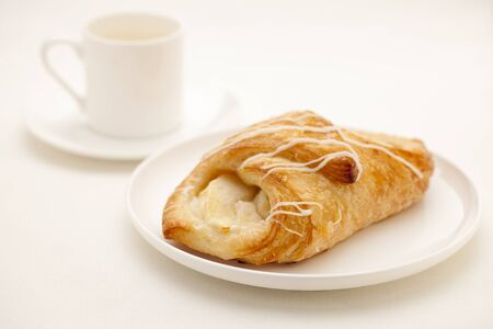 apple croissant pastry on white plate with a cup of espresso coffee in background Stock Photo - 9157404