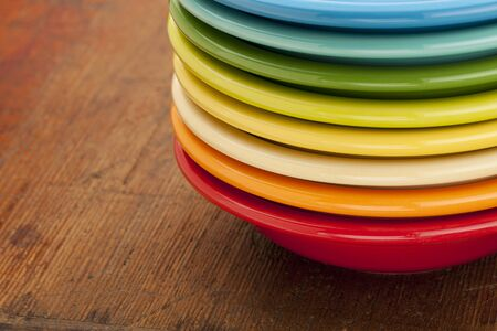 stack of colorful ceramic bowls against an old scratched wooden table surface Stock Photo - 9157420